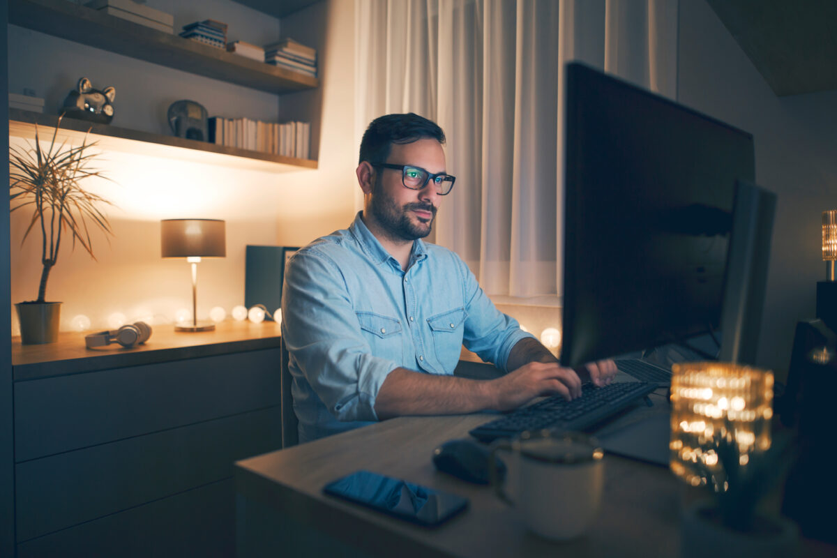 Picture of a person working on a computer at home
