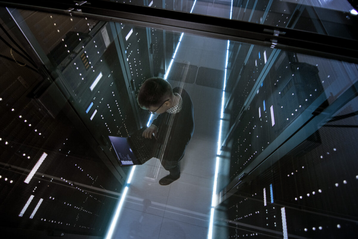 A person holding a laptop doing maintenance on a mainframe computer
