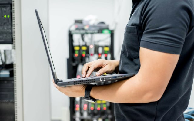 A person working on a laptop in a computer server room